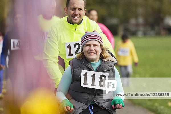 Portrait Mann schiebt lächelnde Frau im Rollstuhl beim Charity-Rennen im Park