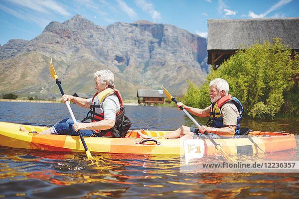 Aktives Kajakfahren für Senioren auf dem sonnigen Sommersee