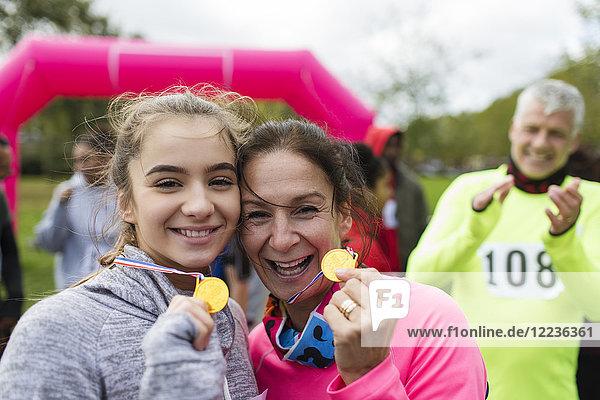 Porträt lächelnde  selbstbewusste Läuferinnen und Läufer mit Medaillen beim Benefizlauf