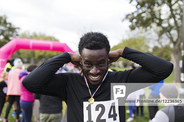 Portrait lächelnder  selbstbewusster Läufer mit Medaille beim Charity-Lauf im Park