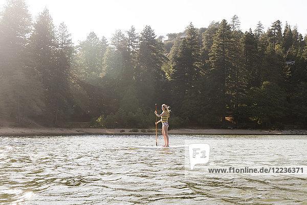 Frau beim Paddeln auf dem sonnigen  ruhigen See