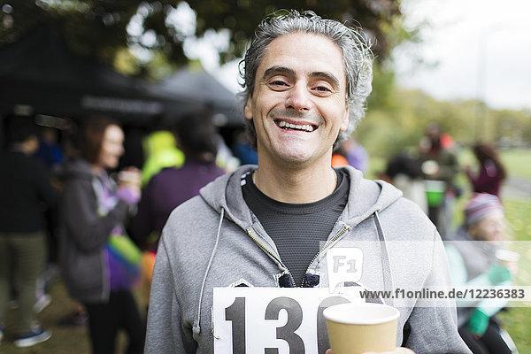 Portrait lächelnder Marathonläufer Trinkwasser