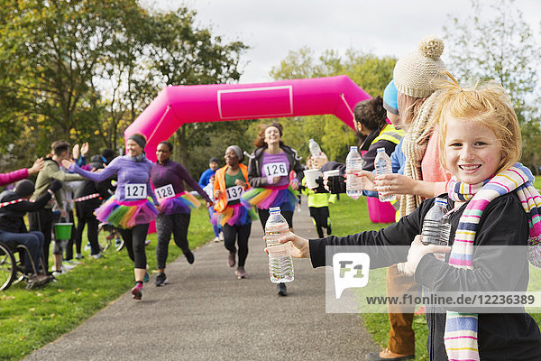 Portrait lächelndes Mädchen mit Wasser für Läufer beim Benefizlauf im Park
