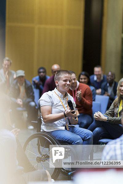 Lächelnde Frau im Rollstuhl spricht mit Mikrofon im Publikum