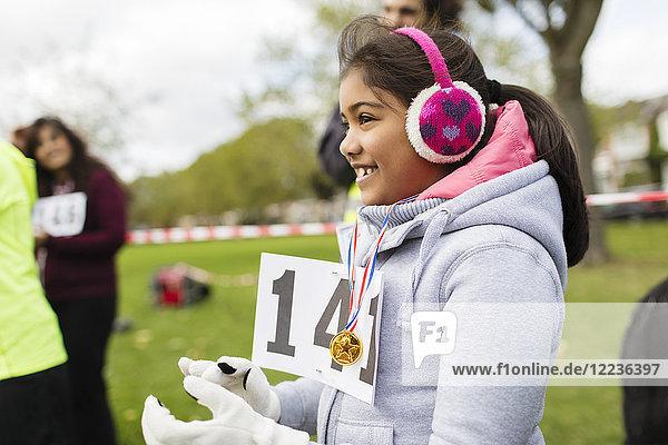 Lächelnde Läuferin mit Ohrenschützern beim Benefizlauf im Park
