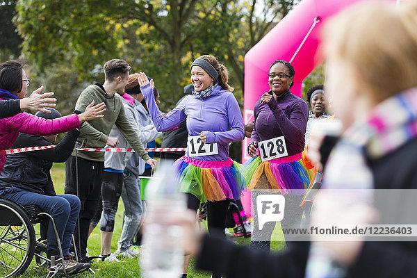 Weibliche Läuferinnen mit hochkarätigen Zuschauern beim Charity-Lauf im Ziel