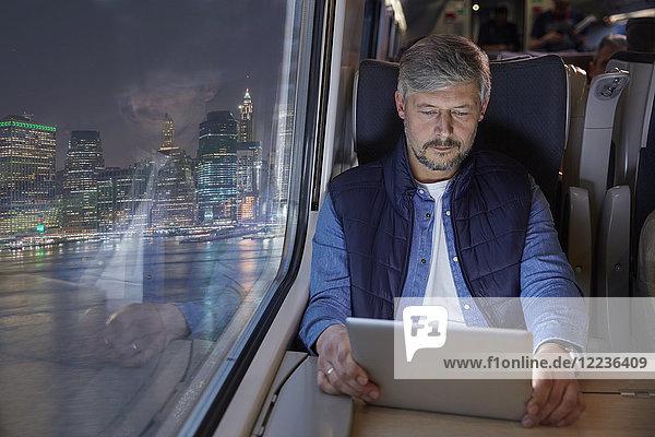 Mann mit digitalem Tablett im Personenzug bei Nacht
