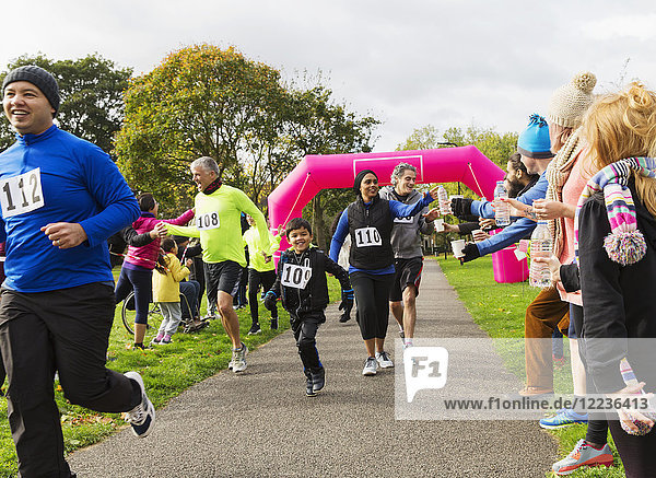 Läufer  die nach Wasser greifen  laufen beim Charity-Lauf im Park.