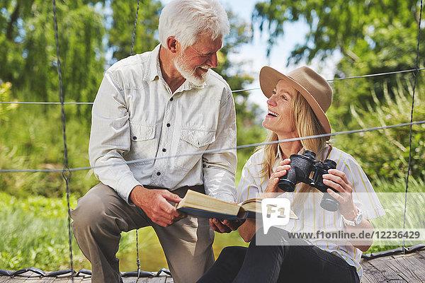 Lächelndes aktives Ehepaar Vogelbeobachtung mit Fernglas und Buch