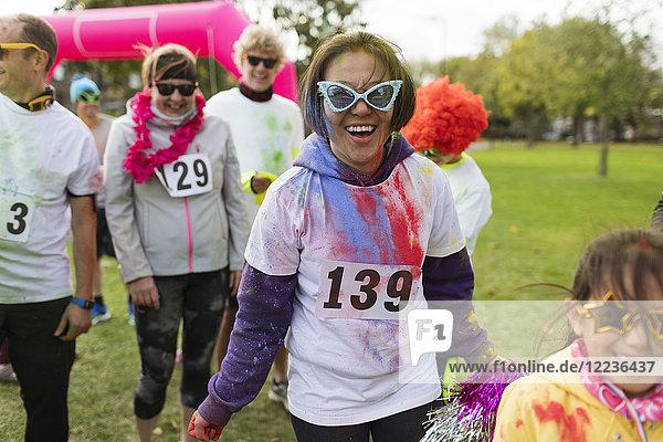 Portrait lächelnde  verspielte Läuferin mit alberner Sonnenbrille beim Charity-Lauf im Park
