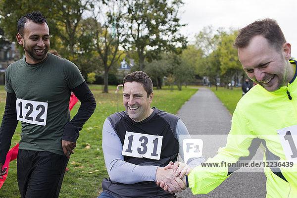 Lächelnder Läufer mit Freund im Rollstuhl beim Benefiz-Rennen im Park