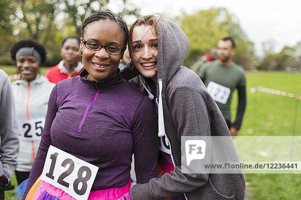 Portrait lächelnde  selbstbewusste Läuferinnen beim Benefizlauf im Park