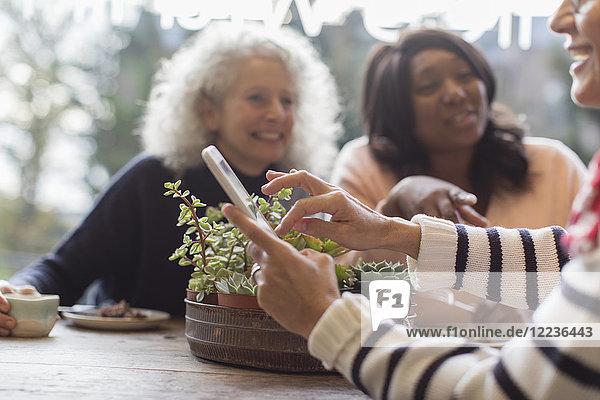 Lächelnde Freundinnen mit Smartphone im Cafe