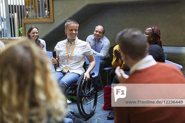 Publikum lächelnd  weibliche Sprecherin mit Mikrofon im Rollstuhl hörend Publikum lächelnd, weibliche Sprecherin mit Mikrofon im Rollstuhl hörend