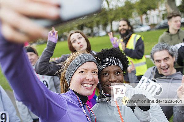 Lächelnde Läuferinnen mit Medaille beim Charity-Lauf im Park