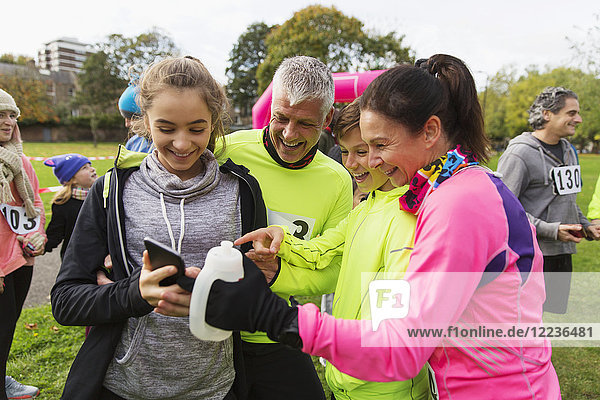 Familienläufer mit Smartphone beim Benefizlauf im Park