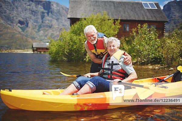 Portrait lächelndes aktives Seniorenpaar beim Kajakfahren auf dem sonnigen Sommersee