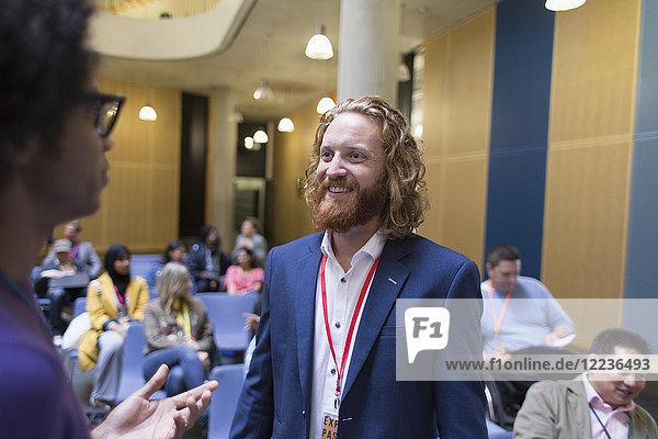 Geschäftsmann im Gespräch mit Kollegen auf der Konferenz Geschäftsmann im Gespräch mit Kollegen auf der Konferenz