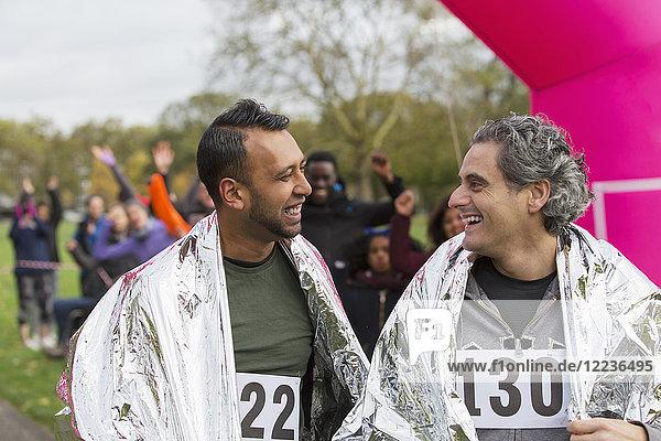 Lächelnde männliche Marathonläufer im Ziel in Thermodecken gehüllt