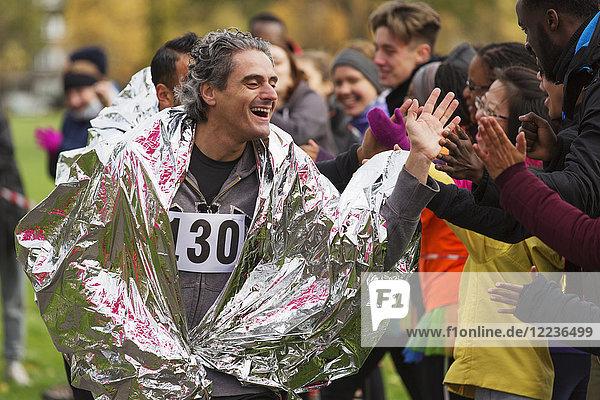 Enthusiastischer männlicher Marathonläufer in Thermodecke mit fünffachem Publikum