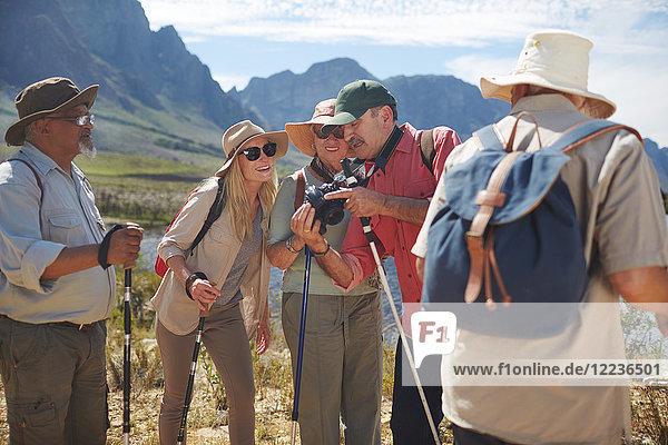 Aktive Seniorenfreunde mit Digitalkamera Wandern mit Wanderstöcken