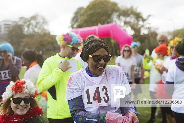 Lachende Läuferin  bedeckt mit heiligem Pulver beim Benefizlauf im Park