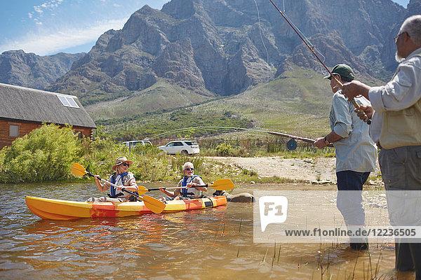 Aktive Seniorenfreunde beim Angeln und Kajakfahren am sonnigen Sommersee