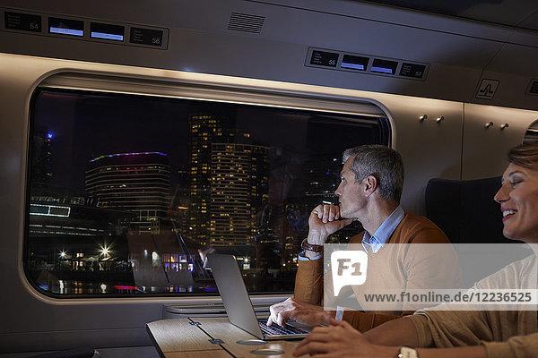 Geschäftsmann arbeitet nachts am Laptop im Personenzug und schaut aus dem Fenster auf die vorbeifahrende Stadt.