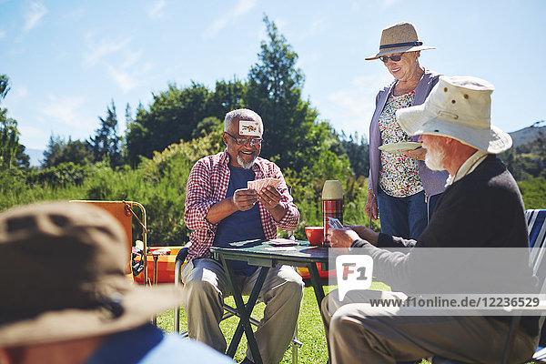 Spielerisch aktive Seniorenfreunde beim Kartenspielen auf dem sonnigen Sommercampingplatz
