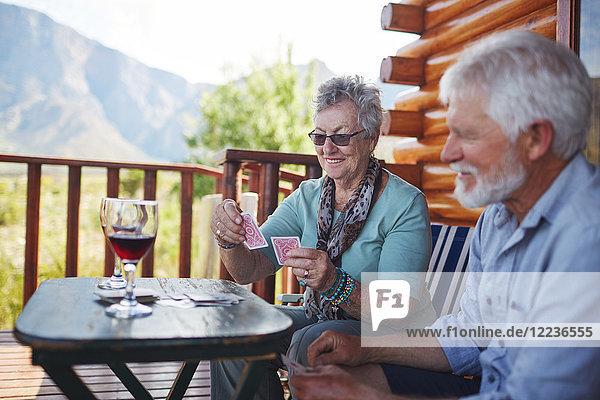 Aktives Seniorenpaar trinkt Wein und Spielkarten auf dem Hüttenbalkon