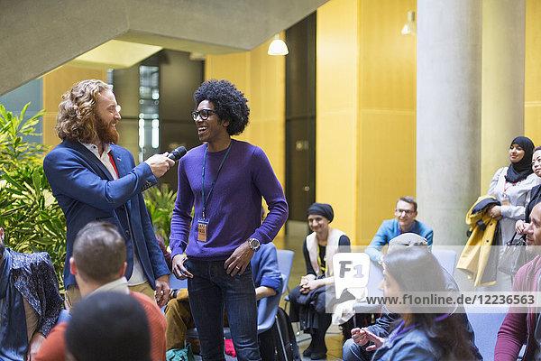 Zuschauer beobachten Redner und Mann im Gespräch mit dem Mikrofon