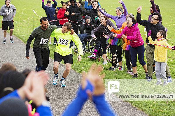 Mann hilft verletzten Läufer beenden Charity-Lauf im Park
