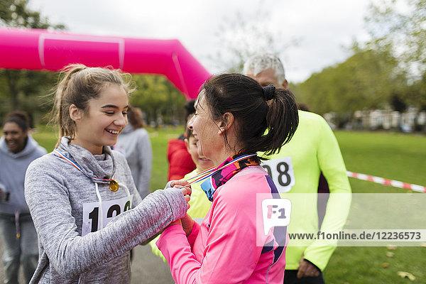 Tochter platziert Medaille um den Hals der Mutter beim Benefizlauf im Park
