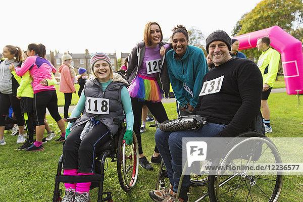 Portrait lächelnde Freunde im Rollstuhl beim Charity-Rennen im Park