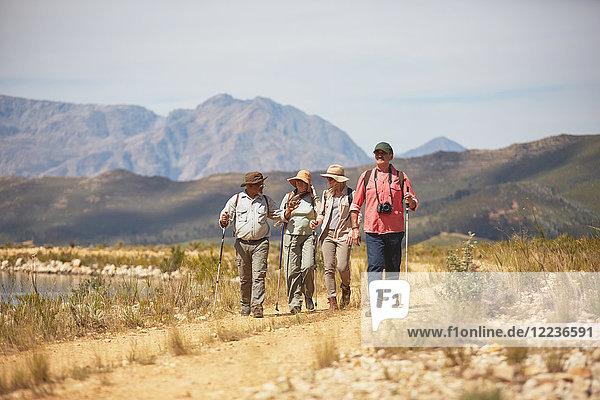 Aktive Seniorenfreunde beim Wandern durch die trockene Sommerlandschaft
