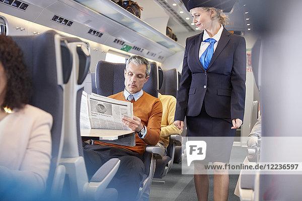 Begleiterin bei der Kontrolle des Geschäftsmannes beim Lesen der Zeitung im Personenzug