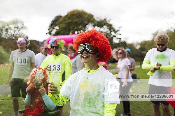 Verspielter Junge Läufer mit Perücke in heiligem Pulver beim Charity-Lauf im Park