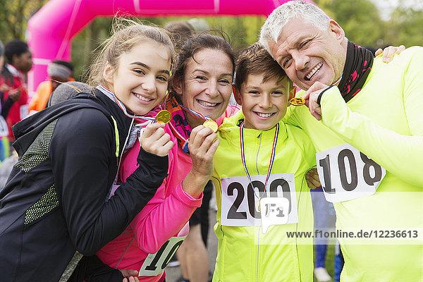 Porträt lächelnde  selbstbewusste Familienläufer mit Medaillen beim Benefizlauf