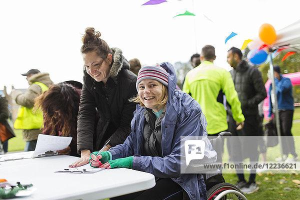 Portrait lächelnde Frau im Rollstuhl beim Einchecken für ein Wohltätigkeitsrennen im Park