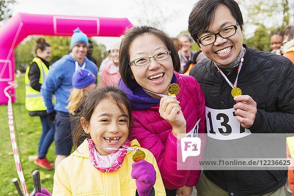 Porträt begeisterter Familienläufer mit Medaillen beim Benefizlauf