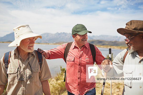 Aktive Seniorenfreunde beim Wandern am sonnigen Seeufer