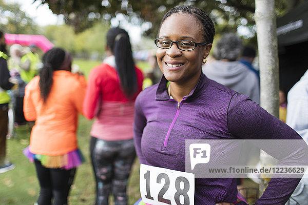 Portrait lächelnde  selbstbewusste Läuferin beim Benefizlauf