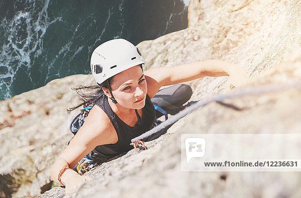 Fokussierte  zielstrebige  weibliche Klettererin beim Klettern