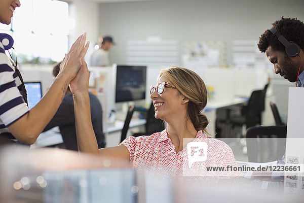 Enthusiastic  confident businesswomen high-fiving in office