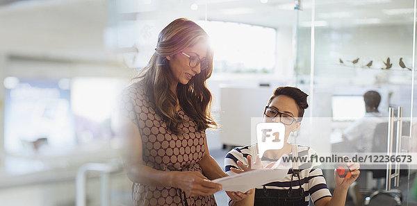 Creative businesswomen planning  discussing paperwork in office