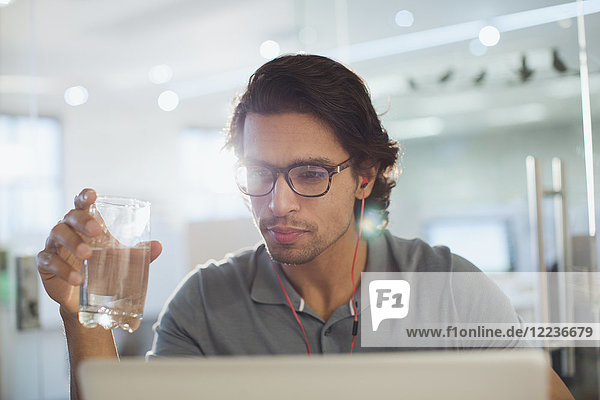 Focused businessman with headphones drinking water at laptop