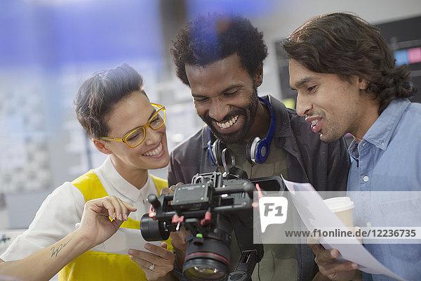 Smiling journalists and cameraman using digital camera