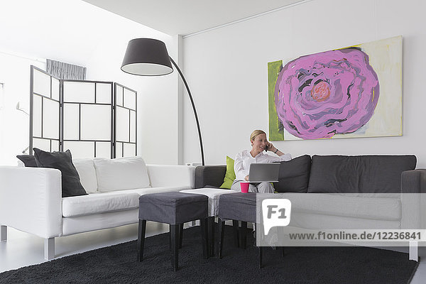 Mature woman sitting in modern living room