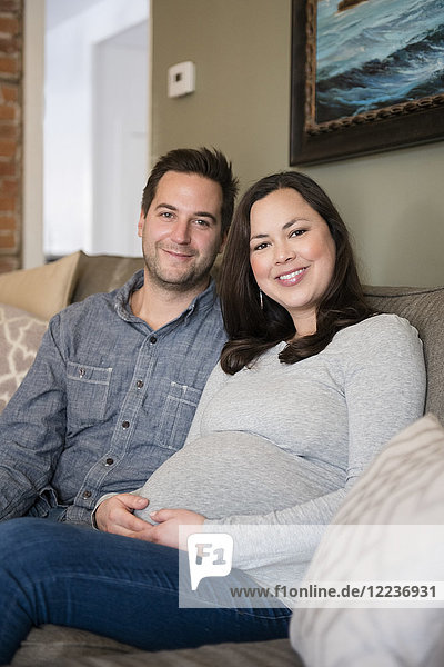 Mid adult couple sitting on sofa and smiling to camera