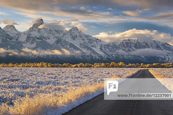 USA  Wyoming  Country road and Teton Range at sunset
